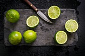 Whole and cut limes on black slate board with vintage knife