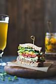 Sandwich mit Tempeh-Speckersatz, Salat, Tomate, Kimchi und Avocado