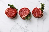 Raw fresh marbled meat Steak filet mignon and thyme on white marble background