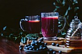 A glass of blueberry hot toddy garnished with a lemon slice