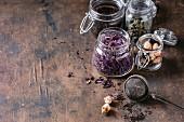 Schwarzer und grüner Tee, Rooibos, Kräutertee und getrocknete Rosenknospen in Gläsern