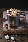 Hot chocolate with homemade marshmallow, chocolate chips and syrup in metal mug