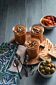 Gazpacho in glasses with grilled flatbread, olives and red and yellow pepper