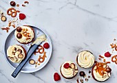 Crackers and salt spread with cream, raspberries and chocolate