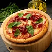 Eine ganze Pizza mit Mozzarella, Schinken und Basilikum