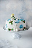 A Christmas cake on a white cake stand