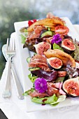 A salad with pears poached in red wine, halloumi, pecans and Parma ham