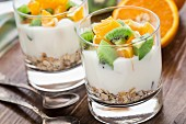 Yogurt with muesli, kiwi and orange in a glass