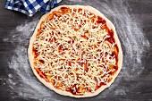 Pizza zubereiten: Pizza mit Käse bestreut (Aufsicht)