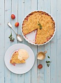 Plum pie with a crumble topping on a blue board