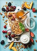 Oat granola in open glass jar, yogurt, fruit, berries, honey and mint on white ceramic board