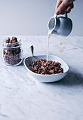 Woman pouring almond milk into a bowl of homemade chocolate granola with oats, nuts and seeds