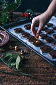 Woman putting orange zest on top of freshly baked chocolate cookies