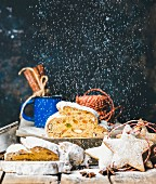 Piece of Traditional German Christmas cake Stollen with festive gingerbread star shaped cookies and falling sugar powder