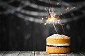 Mini-Kuchen mit brennender Wunderkerze