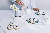 A woman pouring milk into a tea cup on a table with snowmen cookies served on two plates and white flowers in a vase