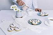Schneemann-Plätzchen auf Tisch, im Hintergrund giesst Frau Milch in Teetasse