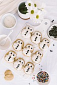 Snowmen cookies with a cute decoration served on a white marble serving board and white flowers aside