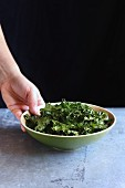 Female hand holding a bowl with baked kale chips