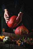 Assortment of different edible and decorative pumpkins and autumn berries in wooden box over wooden background