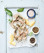 Fresh uncooked shrimps with lemon, herbs, ice and spices on rustic blue wooden board backdrop
