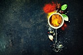 Herbs and spices selection (turmeric, paprika, basil, salt, papper) on dark rustic background