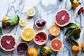 Grapefruits, Zitronen und Orangen, ganz und halbiert auf Marmoruntergrund