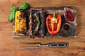 Gegrillte BBQ-Schweinerippchen mit Maiskolben, Paprika und Barbecue-Sauce