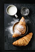 Two fresh baked croissants with sugar powder served with aluminum cup of milk