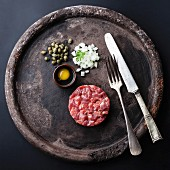 Steak Tartare with capers and fresh onions on black textured background