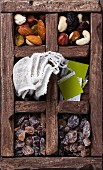 Tea bags, nuts, raisins, brown sugar in wooden box