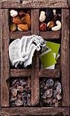 Teebeutel, Nüsse, Rosinen und brauner Zucker in Holzkiste