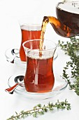 Tea thymus pour into glass cup on white background