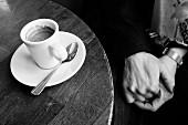 Händchen haltendes Paar mit Espresso in Pariser Cafe (schwarz-weiss-Aufnahme)