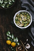 A bowl filled with lemon juice, lemon slices, and peeled baby artichokes