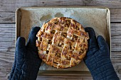 A freshly baked (still warm) caramel apple pie is placed on the table by a person wearing oven mitts