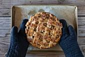 Karamell-Apfelpie wird mit Ofenhandschuhen vom Blech genommen