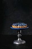 Zitronentörtchen mit Blaubeeren auf Vintage-Kuchenständer vor schwarzem Hintergrund