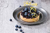 Round Lemon Tart with fresh and cooked blueberries, served on vintage metal plate with lemon zest