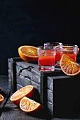 Shortdrinks mit Blutorangensaft auf Holzkiste vor schwarzem Hintergrund