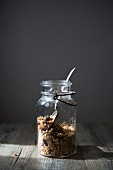 Jar of Homemade Granola with Nuts, Seeds Raisins and Cranberries with Spoon