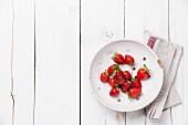 Erdbeeren im Vintage Keramiksieb auf weißem Holzuntergrund