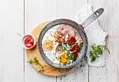 Frühstück mit Spiegeleiern und Wurst in einer Pfanne