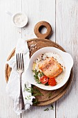 Baked salmon in a bowl on a wooden board