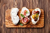 Three bruschettas with mozzarella cheese, ham and roasted tomatoes on ciabatta bread on wooden background