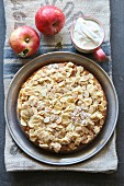 Apple and almond cake on an aluminum plate with a bowl of whipped cream