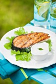 Gegrilltes Lachssteak auf Salatblätter und Knoblauchsauce