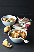 Meatballs soup in a bowl on black background