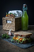 Vegan sandwiches for picnic with roasted carrots, pea spread, and green leafs