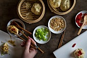 Woman s hand with chopsticks dipping stuffed dumpling in sauce on wooden tabletop with bamboo steamers